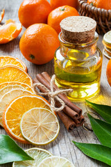 Bottle of essential citrus oil, dried orange and lemon slices, c