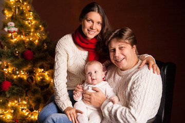 Happy family near Christmas tree at home