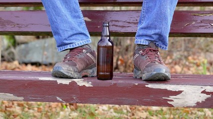 Beer bottle near man's dirty boots