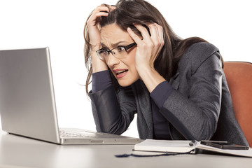 shocked young businesswoman looking in her laptop
