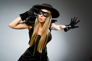 Woman wearing mask against dark background