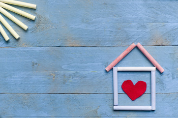 house made of chalk with sun on blue wooden background