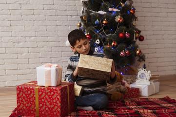 Мальчик раскрывает новогодние подарки