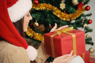 beautiful young woman with present box in santa hat on Christmas