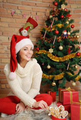 beautiful young woman with present boxes and cookies in Santa ha