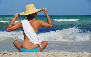 Young woman sitting on the mediterranean beach on hot summer day