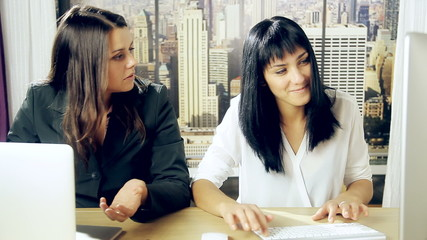 Two business women fighting in office hitting each other