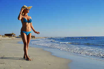 Woman standing on the mediterranean beach on hot summer day