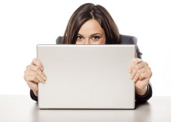 young happy beautiful businesswoman peek behind her laptop