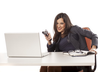 young beautiful businesswoman aim with a gun on her workplace
