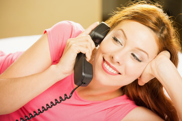 happy smiling woman talking on a phone lying in bed