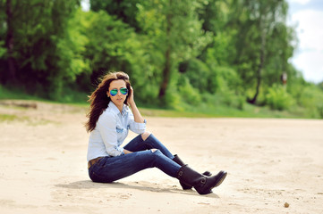 Sexy young woman sitting on a beach outdoor fashion portrait