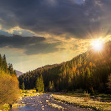 Fototapety forest river in mountains with stones at sunset