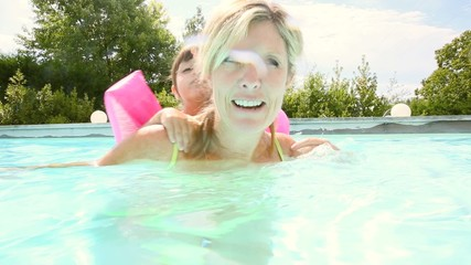 Mother and daughter swimming in private pool