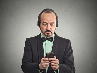 man listening to music on smartphone with pair of headphones