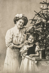 happy mother and daughter with christmas tree and antique toys