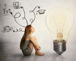 woman sitting in front of lightbulb thinking has many thoughts