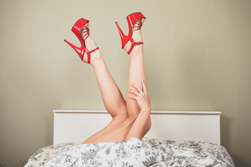 Woman wearing heels in bed