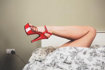 Woman wearing heels in bed