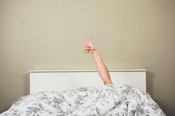Woman in bed giving thumbs up