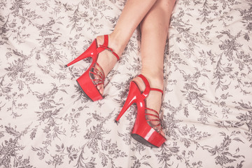 Woman wearing red heels in bed
