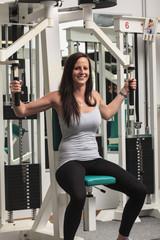 junge Frau an einem Sportgerät im Fitness-Studio