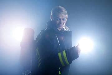 Junge motivierte Feuerwehr Frau hält Daumen hoch im Rauch
