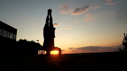 Young muscular man in tank top doing hand stand at park during