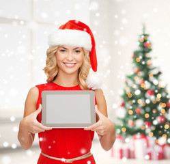 woman in santa helper hat showing tablet pc screen