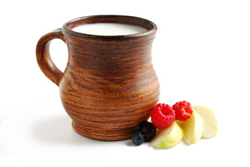 Milk in ceramic bowl and summer fruits