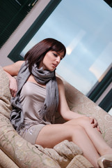 women with beautiful legs and cute face relaxing on couch