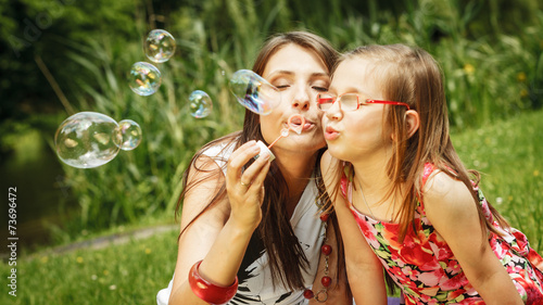 canvas print picture Mother and little girl blowing soap bubbles in park.