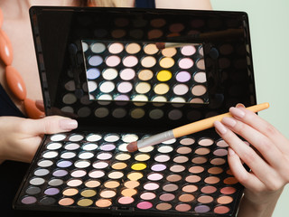 colorful eyeshadows palette, makeup brush in female hand
