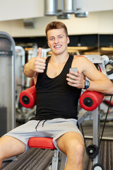 smiling young man with smartphone in gym