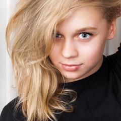 Smiling Caucasian girl with long blond hair, studio portrait