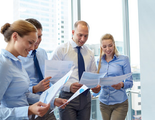 smiling businesspeople with papers in office