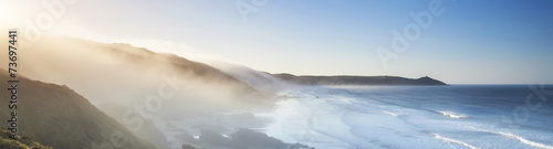 Fotobehang Zonsondergang Amazing panorama of headland and sea fog at sunrise.