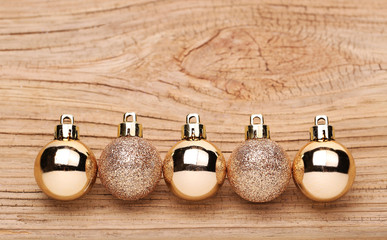 Gold Christmas Balls Over Wooden Background.