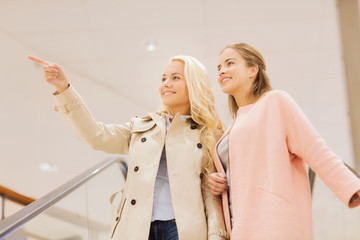 young women pointing finger on escalator in mall