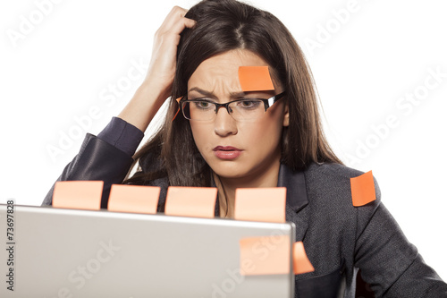 Leinwanddruck Bild confused young businesswoman with stickers on her and her laptop