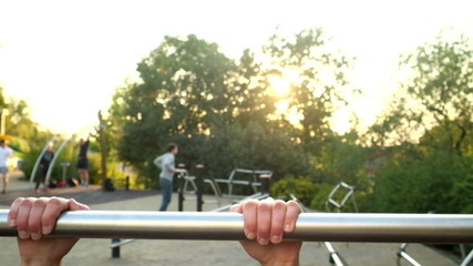 Young muscular man doing pull ups on a bar in park
