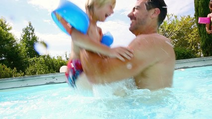 Little boy playing with daddy in swimming-pool