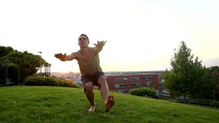 Young muscular man in tank top doing one leg squat at park