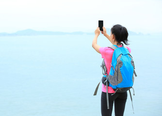 woman hiker use cell phone taking photo on seaside mountain peak