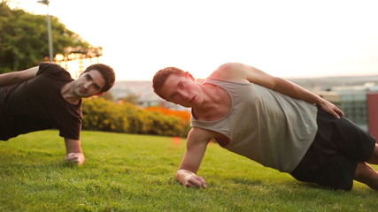 Two Young muscular men doing plank and wotking out in park