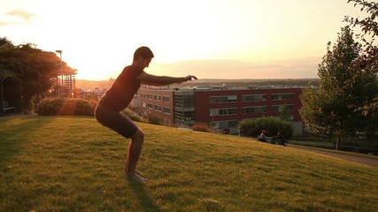Young muscular man doing squats in park during sunset