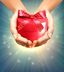 Holiday background with hands holding gift box. Concept of givin