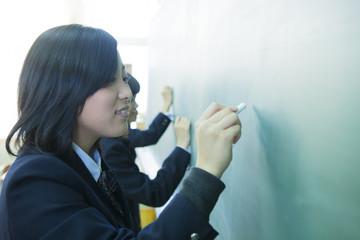 黒板に文字を書く高校生たち