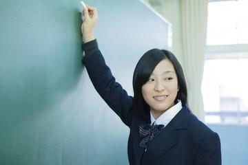 黒板に文字を書く高校生