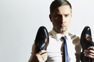 fashion portrait of handsome man holds shoes.Businessman in tie